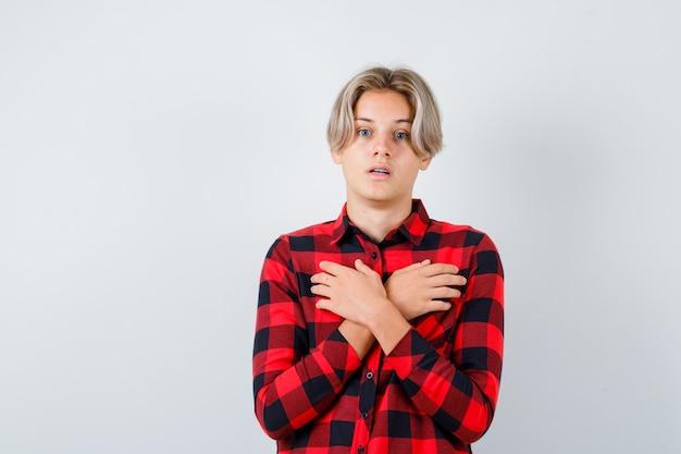 Ritratto di adolescente maschio biondo che tiene le mani incrociate sul petto in camicia casual e sembra scioccato vista frontale