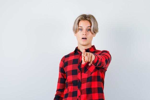 Ritratto di adolescente maschio biondo che punta davanti in camicia casual e guarda perplesso vista frontale