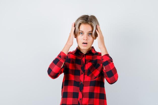 Ritratto di adolescente maschio biondo con le mani vicino alla testa in camicia casual e guardando sconcertato vista frontale