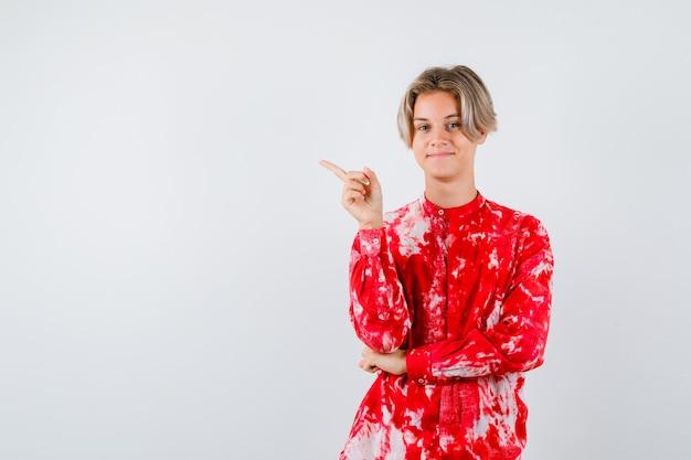 Ritratto di adolescente maschio biondo che punta all'angolo in alto a sinistra in una camicia sovradimensionata e sembra una vista frontale allegra