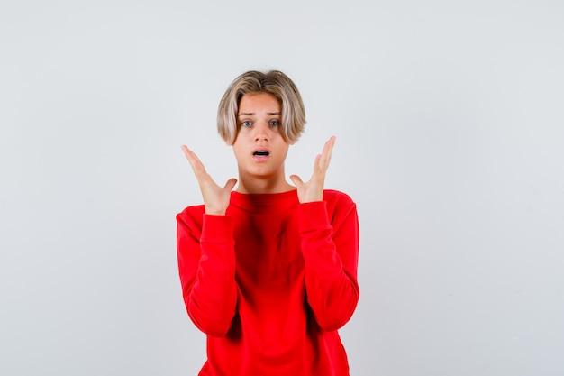 Ritratto di adolescente maschio biondo con le mani vicino al viso in maglione rosso e guardando confuso vista frontale