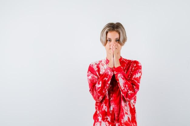 Ritratto di adolescente biondo maschio con le mani in gesto di preghiera in camicia oversize e guardando speranzoso vista frontale