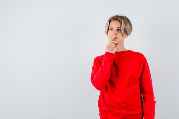 Ritratto di ragazzo adolescente in piedi in posa di pensiero in maglione rosso e guardando pensieroso vista frontale