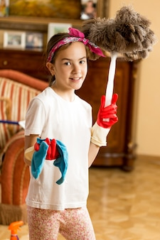 Ritratto di ragazza adolescente che pulisce il soggiorno con un panno e una spazzola di piume feather
