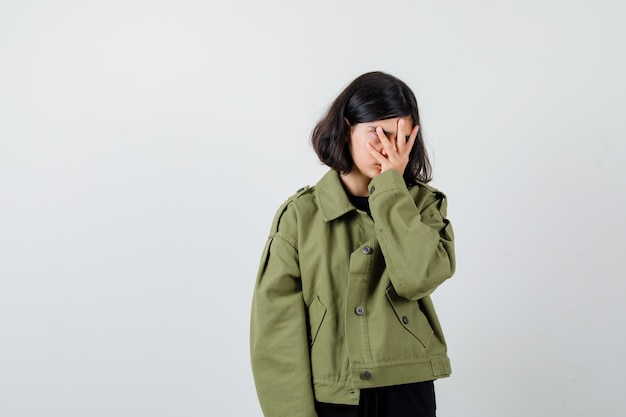 Ritratto di ragazza adolescente che tiene la mano sul viso in giacca verde militare e sembra vista frontale esausta