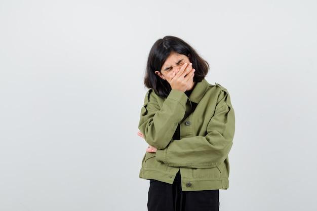 Ritratto di una ragazza adolescente che tiene la mano sulla bocca con una giacca verde militare e guarda una vista frontale addolorata