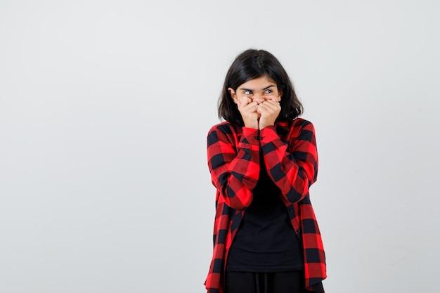 Ritratto di una ragazza adolescente che tiene le mani sul viso, guardando da parte in camicia casual e guardando la vista frontale spaventata