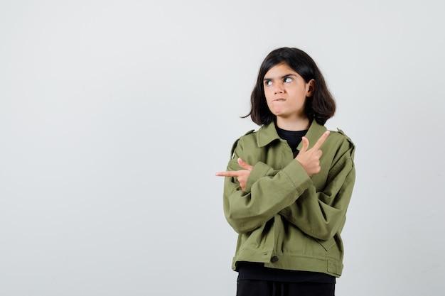 Ritratto di ragazza adolescente che punta nelle direzioni opposte, guardando lontano, mordendosi il labbro in giacca verde militare e guardando la vista frontale esitante