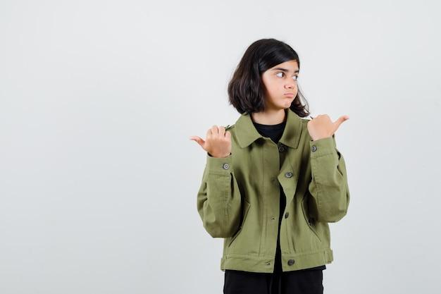 Ritratto di una ragazza adolescente che punta a destra e a sinistra con i pollici, guardando da parte con la giacca verde militare e guardando la vista frontale indecisa