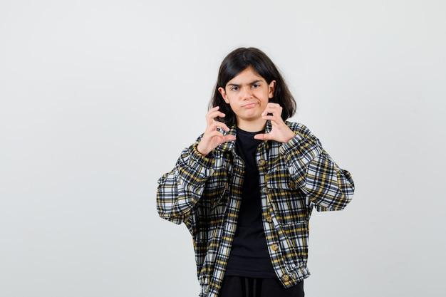 Ritratto di una ragazza adolescente che finge di tenere qualcosa in una camicia casual e sembra una vista frontale sconvolta