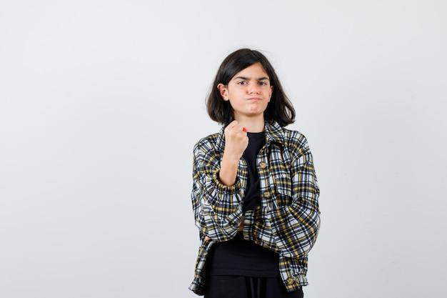 Ritratto di una ragazza adolescente che avverte con il pugno chiuso in una camicia casual e che sembra una vista frontale aggressiva