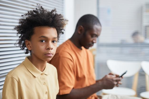 Ritratto di un adolescente afro-americano che guarda la telecamera mentre aspetta in fila presso la clinica medica con il padre, copia spazio