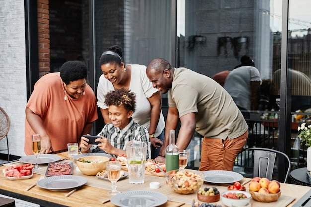 Ritratto di un adolescente afroamericano che mostra i video dello smartphone alla famiglia durante la cena insieme...