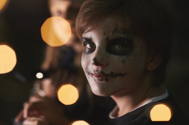 Ritratto di ragazzo adolescente che indossa la vernice per il viso e durante la festa di halloween all'aperto con luci, copia dello spazio