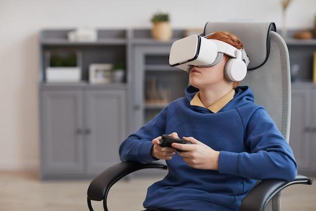 Ritratto di un adolescente che indossa un auricolare vr e tiene in mano il gamepad mentre gioca a videogiochi immersivi, copia spazio