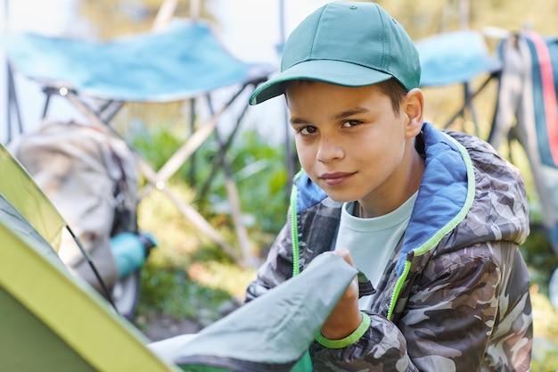 Ritratto di ragazzo adolescente durante l'impostazione della tenda durante il campeggio in famiglia, copia dello spazio