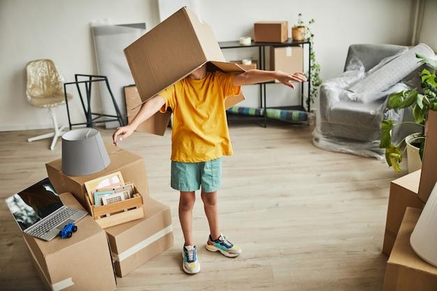 Ritratto di ragazzo adolescente con scatola sulla testa che gioca con le cose mentre la famiglia si trasferisce in una nuova casa copia s...