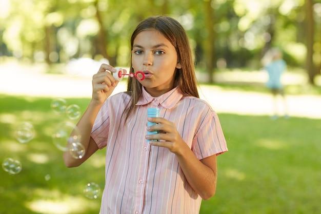 Ritratto di ragazza adolescente a soffiare bolle mentre si sta in piedi nel parco verde all'aperto