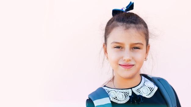 Ritratto di ragazza adolescente pronta per la scuola su sfondo rosa pastello.