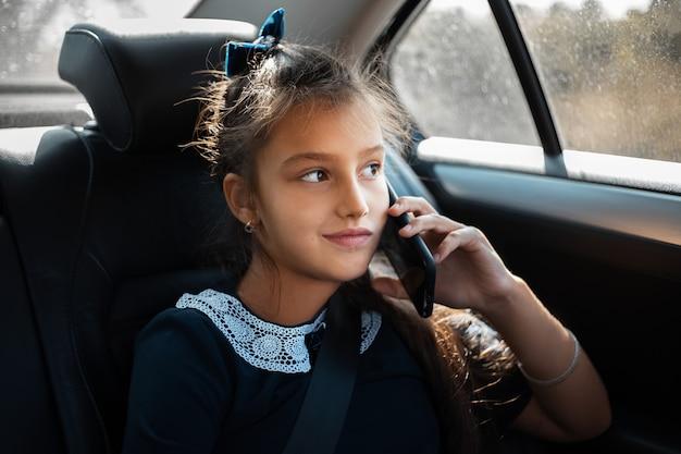 Ritratto di un'adolescente che parla allo smartphone sul sedile posteriore dell'auto.