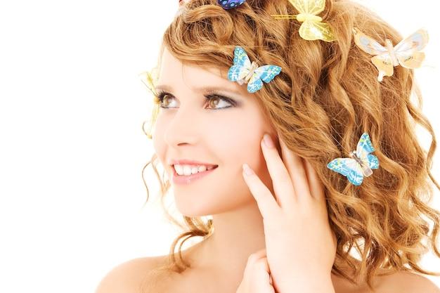 Ritratto di una ragazza adolescente con farfalle sul muro bianco