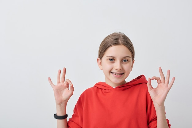 Ritratto dell'adolescente con le parentesi graffe dentali che indossa la felpa con cappuccio rossa che mostra segno giusto