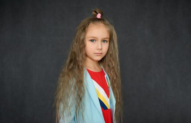 Ritratto di una ragazza adolescente con capelli ricci sciolti su uno sfondo scuro