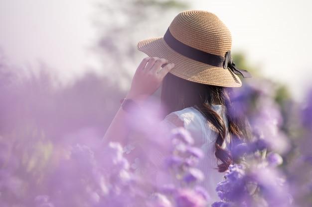 Il ritratto degli adolescenti è felice nel fiore del margaret in giardino molti colori di mattina.