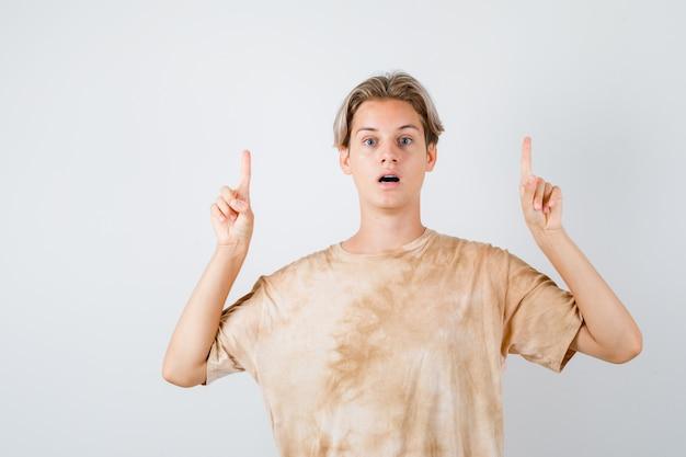 Ritratto di un ragazzo adolescente che punta in alto in maglietta e guarda ansioso vista frontale