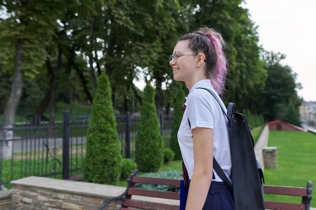 Ritratto di una ragazza adolescente con lo zaino che va a scuola, mattina d'autunno d'estate, sfondo dell'edificio scolastico. ritorno a scuola, ritorno al college