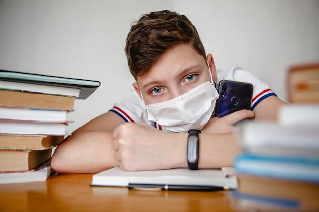 Ritratto di un adolescente a casa in una maschera dietro i libri di testo
