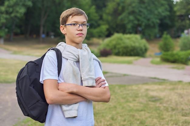 Ritratto dello scolaro dell'adolescente in vetri con lo zaino