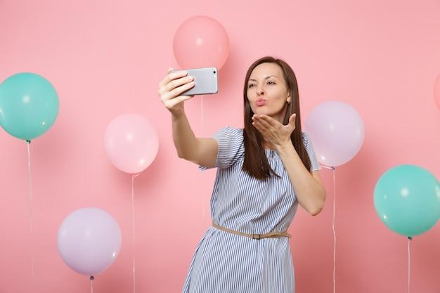 Ritratto di una donna tenera e attraente in abito blu che fa selfie sul cellulare inviando un bacio d'aria su sfondo rosa pastello con mongolfiere colorate. festa di compleanno, persone sincere emozioni.