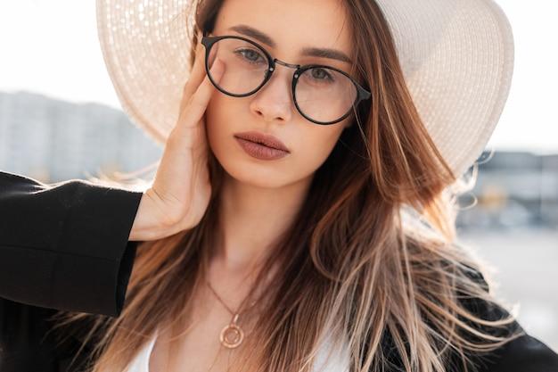 Giovane donna attraente tenera del ritratto con pelle sana pulita con belle labbra sexy con gli occhi stupefacenti in cappello in vetri in giacca il giorno pieno di sole all'aperto. la ragazza abbastanza urbana gode della passeggiata e della luce solare.