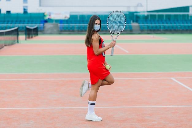 Ritratto della ragazza del giocatore di tennis che tiene la racchetta all'esterno con maschere protettive