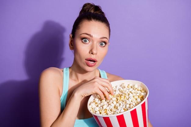 Ritratto di ragazza terrorizzata che mangia mais guardando film di genere thriller