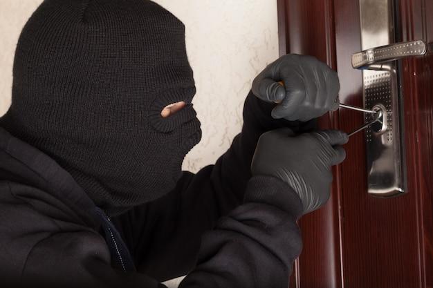 Ritratto di un ladro che usa gli strumenti sul buco della serratura