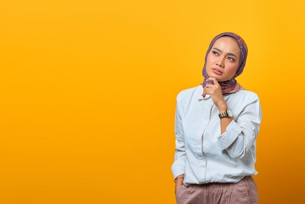 Ritratto di una donna asiatica pensante che tocca il mento e guarda uno spazio vuoto su sfondo giallo