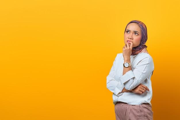 Ritratto di una donna asiatica pensante che tocca le labbra e guarda uno spazio vuoto su sfondo giallo