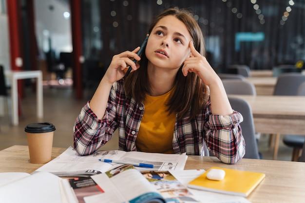 Ritratto di una ragazza caucasica pensante che parla al cellulare mentre fa i compiti con i quaderni nella biblioteca del college