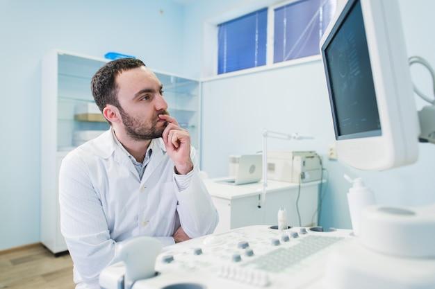 Ritratto di un medico pensante vicino sceen di attrezzature mediche.