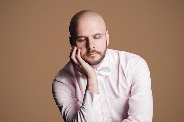 Ritratto di pensare bell'uomo barbuto calvo in camicia rosa chiaro e fiocco bianco, seduto su una sedia che si tocca il viso con la mano e gli occhi chiusi. girato in studio al coperto, isolato su sfondo marrone.