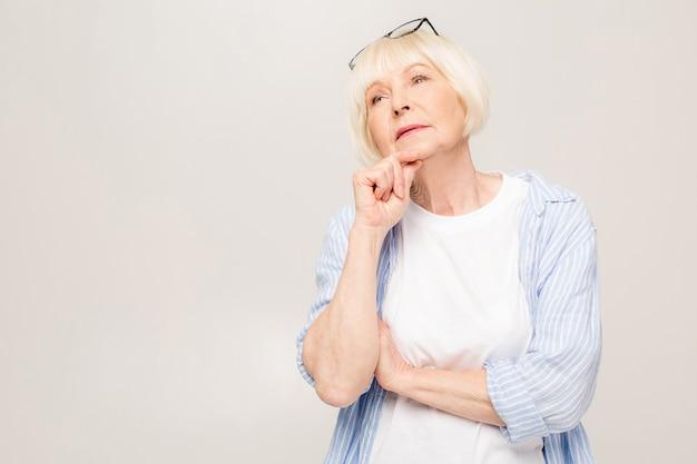 Ritratto di donna senior di pensiero isolata sopra priorità bassa bianca.