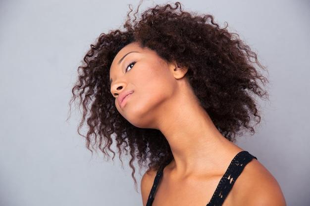 Ritratto di una donna afroamericana premurosa che osserva in su sopra il muro grigio