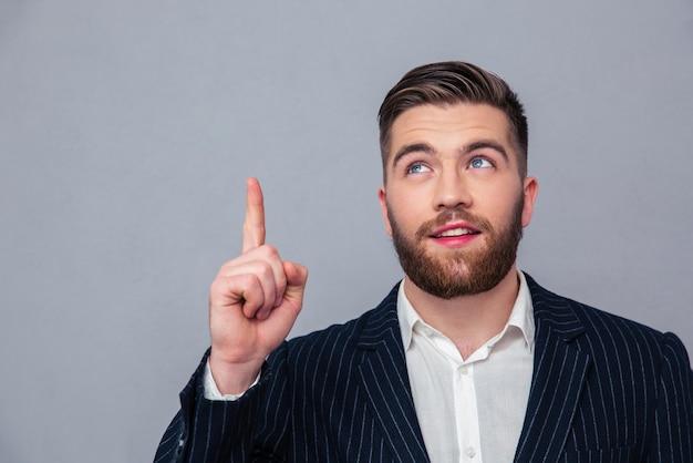 Ritratto di un uomo d'affari premuroso che punta il dito su oltre il muro grigio