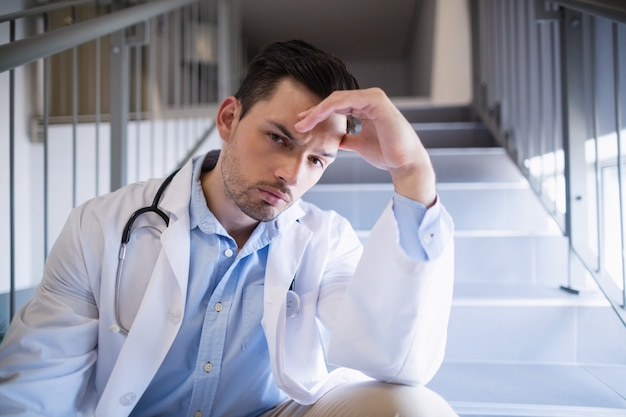 Ritratto di medico premuroso che si siede sulla scala