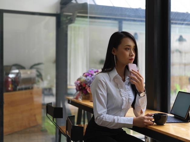 Ritratto di donna premurosa tenendo lo smartphone e la tazza di caffè mentre è seduto al posto di lavoro