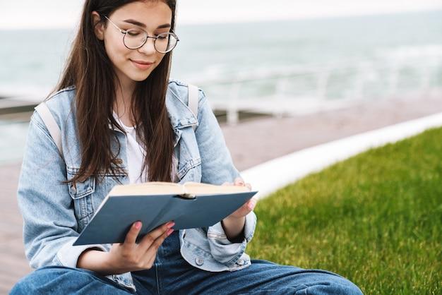 Ritratto di premurosa adorabile ragazza adolescente che indossa occhiali leggendo un libro mentre è seduto sull'erba verde in riva al mare