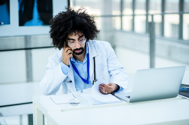Ritratto di medico maschio premuroso con raggi x in ospedale, concetto di virus corona.