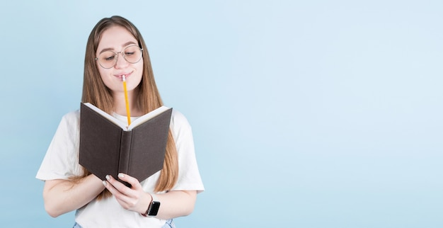Ritratto della ragazza pensierosa premurosa che ha taccuino e matita in bocca. isolato su sfondo blu con copia spazio.